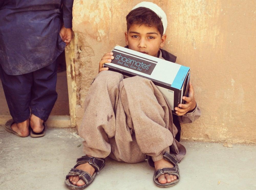 Endlich vernünftige Schuhe - ein afghanischer Junge freut sich